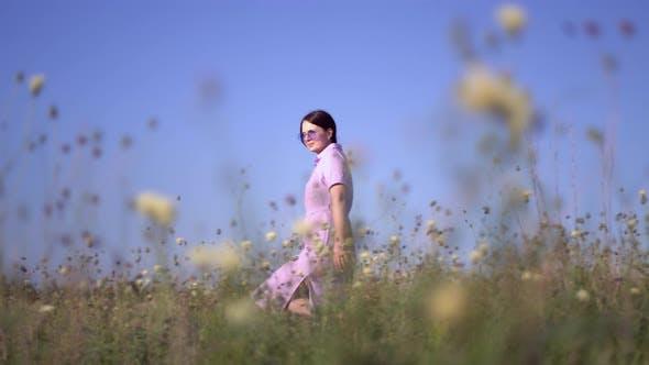 Mädchen in lila Kleid Spaziergänge durch das Feld mit Feldblumen.