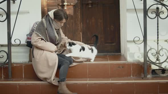 Woman play with homeless cat