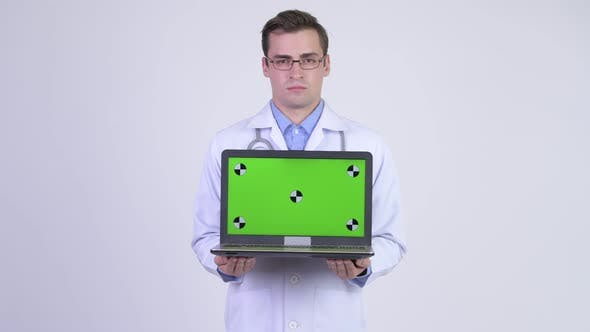 Cover Image for Young Happy Handsome Man Doctor Showing Laptop
