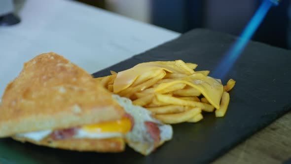 Fast Food, Delicious Sandwich with Fried Egg, Bacon and Fries on Black Plate Melt Cheese with Gas