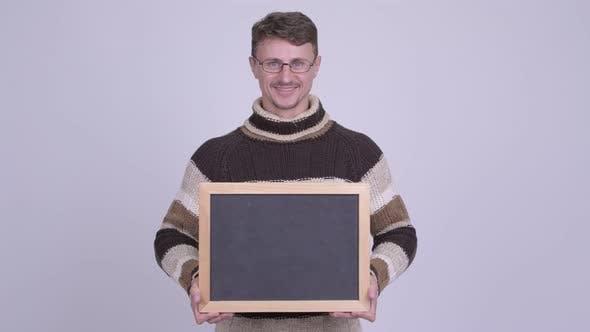 Thumbnail for Happy Handsome Bearded Man Holding Blackboard Ready for Winter