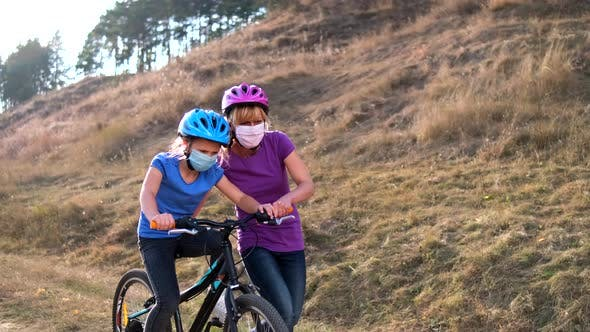 A young mother teaches his daughter to ride a Bicycle in medical masks and a Bicycle helmet