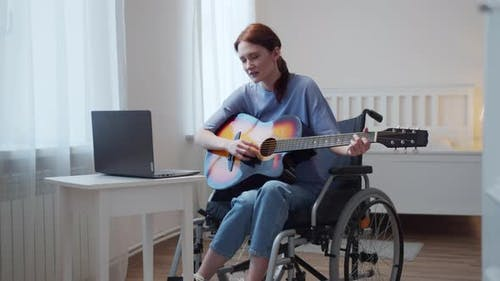 A Young Disabled Lady is Teaching How Playing the Guitar