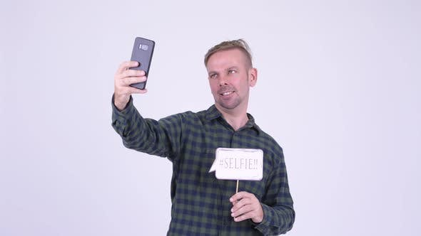 Cover Image for Portrait of Happy Blonde Hipster Man Taking Selfie with Paper Sign