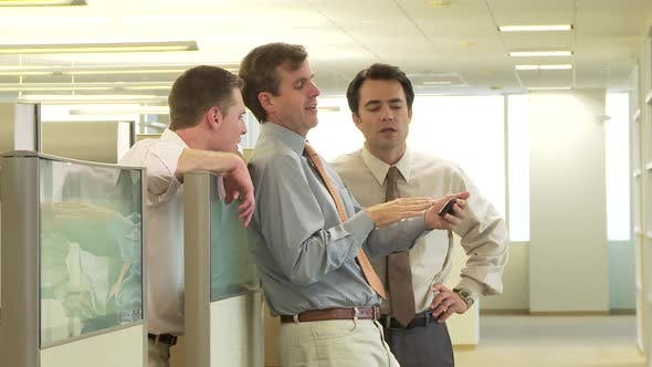 Business colleagues talking by office cubicle