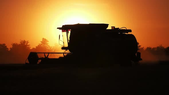 Thumbnail for Advanced Combine Harvester Moving at Shimmering Golden Sunset