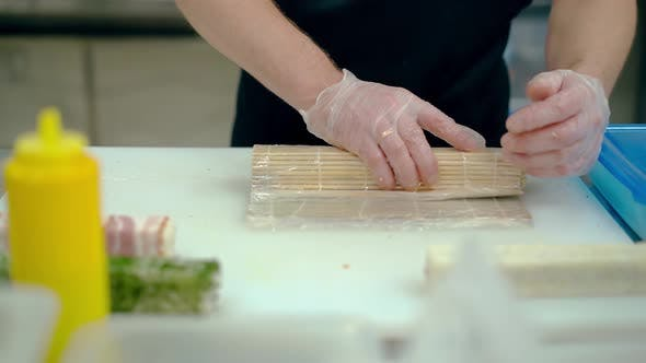 Cook Prepares a Japanese Roll with Rice and Sesame Seeds