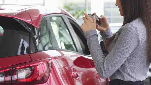 Thumbnail for Cropped Shot of a Woman Taking Photos of Her New Car