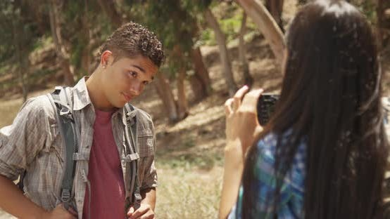 Hispanic girl taking pictures of boyfriend