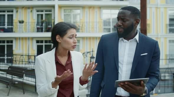 Sad Mixed Race Partners Talking at Street