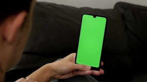 Big green screen display mobile phone in female hand 4K close-up video