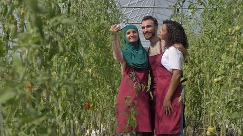 Joyful Diverse Gardeners Taking Selfie in Hothouse