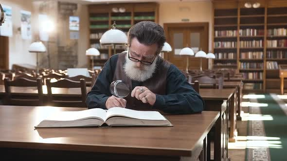 Thumbnail for Old Man in Glasses which Recording Important Notes From the Book, Sitting in the Library