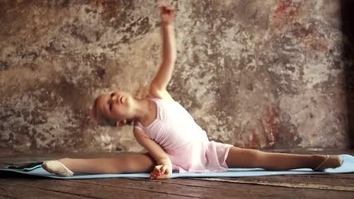 Kid Girl Gymnast Sitting in the Splits and Doing a Warmup