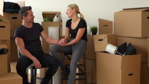 Thumbnail for A Happy Moving Couple Sits on Chairs in an Empty Apartment, Talks and Holds Hands