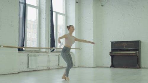 Ballerina Practicing Pirouette in Dance Studio