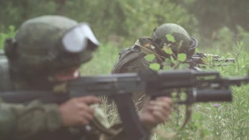 Soldiers in Camouflage with Assault Rifles Out of the Ambush in the Field Military Action