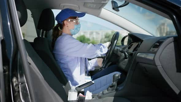 Thumbnail for Health Care, Young Girl Driver in Goggles, Medical Mask and Gloves Works As Courier and Wipes