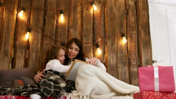 Cover Image for Mom with Little Girl Reading a Book and Relaxing on a Cozy Sofa Under the Christmas Lights