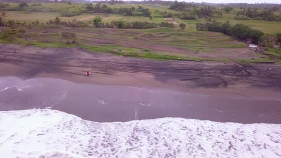 Aerial drone view of a man riding his motocross motorcycle on the beach