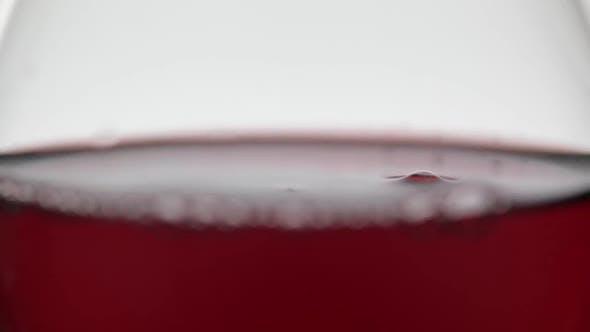 Nahaufnahme eines Tropfen fallen in Glas mit Rotwein. Rosenwein auf weißem Hintergrund
