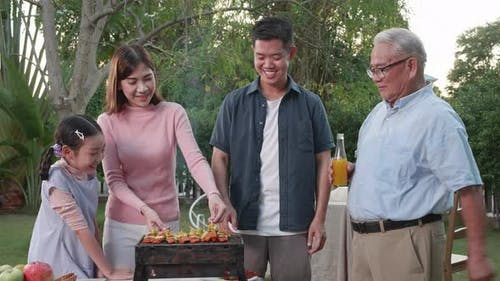 Happy Asian family having a barbecue-BBQ party together in the garden at home.