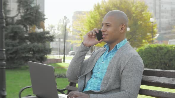 Thumbnail for Handsome African American Businessman Using Smart Phone and Laptop Outdoors
