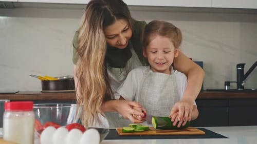 Kid with Mother in Kitchen Learns to Cut Green