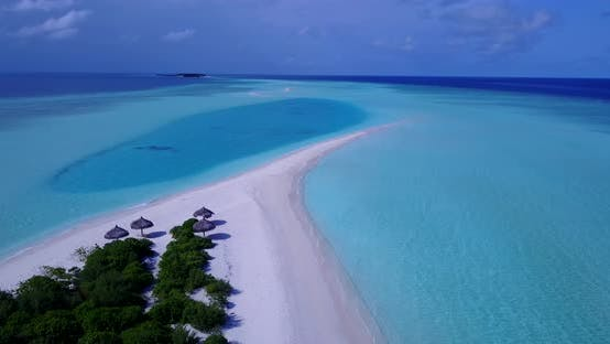 Wide angle drone tourism shot of a sandy white paradise beach and blue water background in vibrant 4