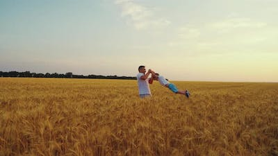 Slow Motion Dad Playing with Son in Field