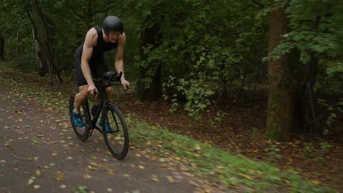 Triathlete Rides a Bike Pro Cyclist Rides on a Forest Road Preparation for Competitions and