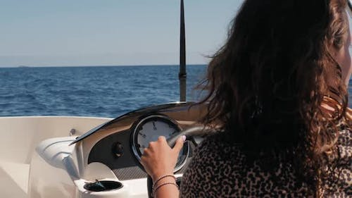 Beautiful Attractive Sailor Girl Driving a Rent Small Boat Yacht