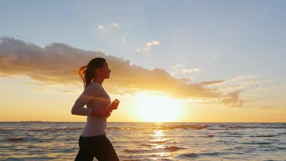 Young Attractive Woman Jogging By the Sea