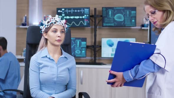 Neurology Doctor Holding Clipboard in Front of Female Patient