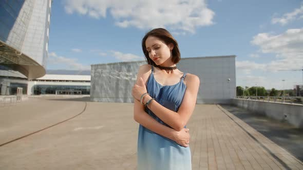 Thumbnail for Beautiful Modest Young Girl Posing With Industrial Background With Glass Buildings