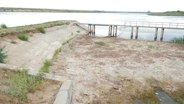 Ecological Disaster. Cracked Soil Ground and Broken Bridge Over Dried Lake or River. Land Destroyed