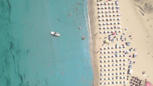 Top View of Sand Beach with Umbrellas Boat and Swimming People in Sea Bay Water