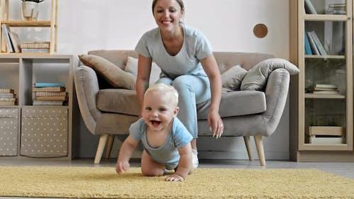 Woman Watching Her Baby Crawling