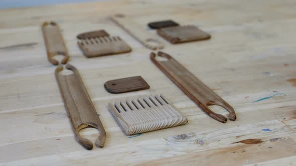 Weaver Puts Tools Scallops and Shuttles on a Wooden Table in the Workshop