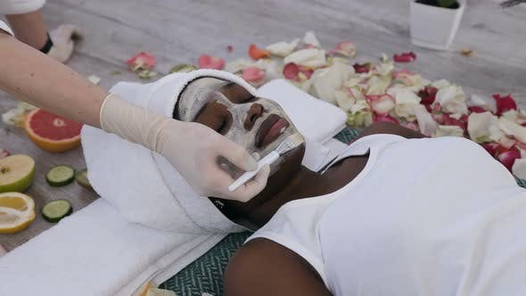 Cover Image for African Woman Getting Facials Care with Help Beautician in Beauty Salon