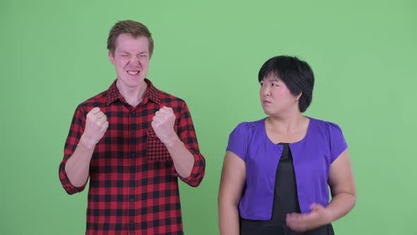 Thumbnail for Happy Scandinavian Hipster Man Giving Thumbs Up with Overweight Asian Woman Looking Confused