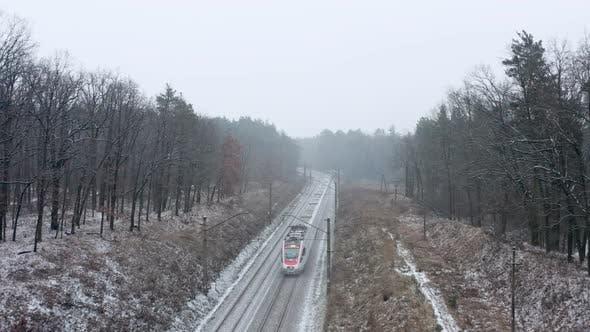 Thumbnail for Passenger train passing through winter forest.