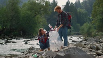 Hikers Cleaning River Shore From Plastic