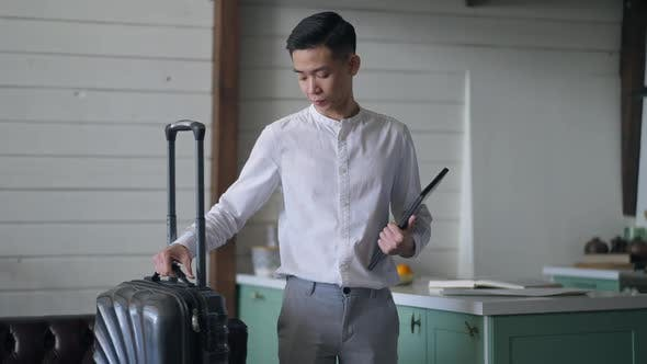 Thoughtful Young Asian Man Leaving in Slow Motion with Travel Bag and Tablet