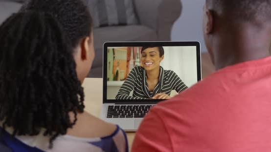 Thumbnail for Young black couple having internet video chat with friend on laptop