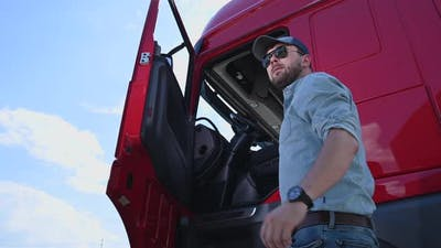 Caucasian Trucker in His 30s Getting Into Modern Semi Truck Cabin. Trucking Theme.