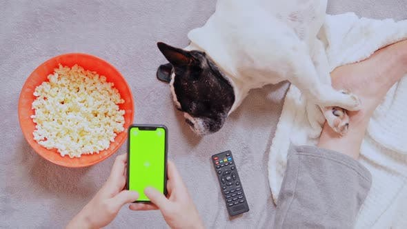 Thumbnail for Man Eating Popcorn Holding Smartphone Indoors