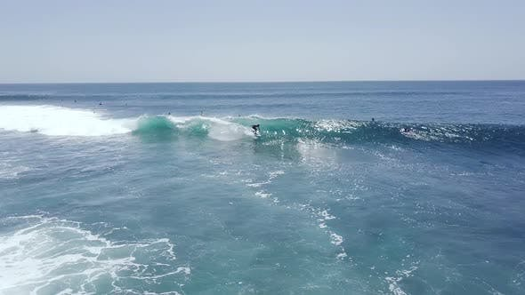 Young Expert Surfers Enjoys Riding the Perfect Big Waves in Emerald Ocean on Summer.