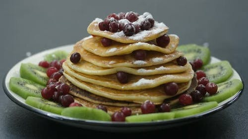 Decorating Pancakes with Berry and Powdered Sugar