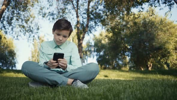 Thumbnail for Teenager Playing Video Games on His Smartphone Outdoors